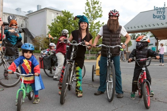 family in costume on bikes