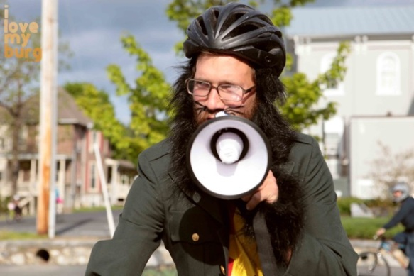 man in cat costume on bike with megaphone