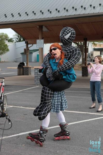 man in spiderman costume, on rollerblades