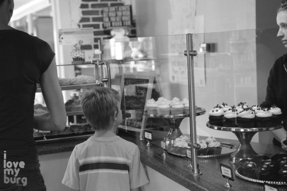 boy looking at cupcake counter