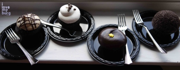 four cupcakes on plates