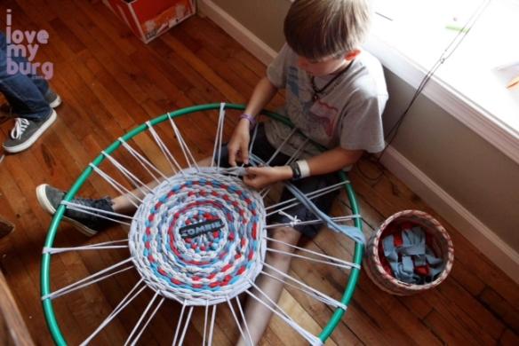 boy weaving hula hoop rug