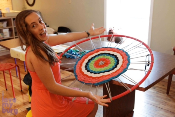 girl weaving hula hoop rug